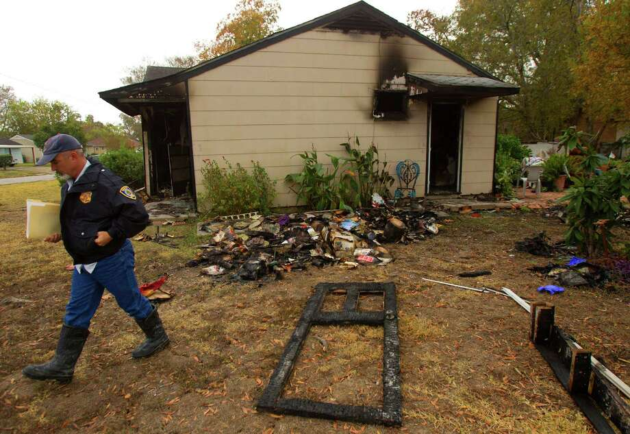 An investigator looks at a home after a fire erupted late Monday night in the 6100 block of Sherwood near Tolnay,Tuesday, Nov. 27, 2012, in Houston. Photo: Cody Duty, Houston Chronicle / © 2012 Houston Chronicle