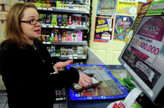 Jamie Robertine, of Shelton, buys lottery tickets for her office pool Tuesday, Nov. 27, 2012 at the BP gas station in Shelton, Conn. Wednesday's Powerball has a jackpot of $500 million. Photo: Autumn Driscoll / Connecticut Post