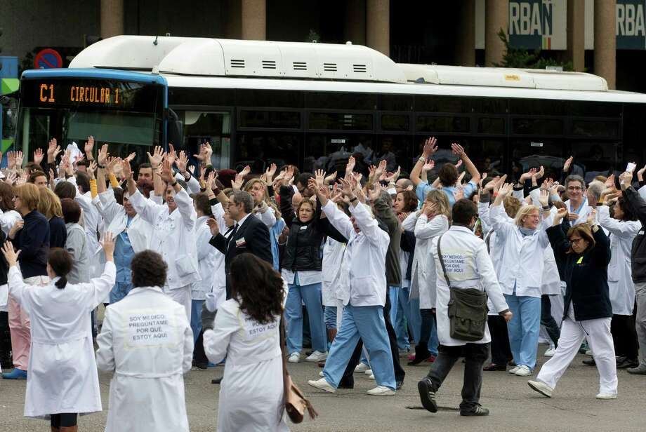 Staff from the Clinico San Carlos hospital block the traffic outside the hospital during a protest against cuts in the national health service in Madrid, Tuesday, Nov. 27, 2012. Spaniards are angered by austerity measures, including budget cuts and plans to partly privatize some of their country's cherished national health service. Words on back of medical coats read: 'I am a doctor - ask me why I am here' (AP Photo/Paul White) Photo: Paul White