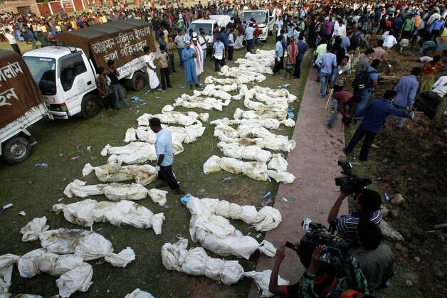 Bangladeshis prepare to bury the bodies of a part of the victims of Saturday's fire in a garment factory in Dhaka, Bangladesh, Tuesday, Nov. 27, 2012. Bangladesh held a day of mourning Tuesday for the 112 people killed in a weekend fire at a garment factory, and labor groups planned more protests to demand better worker safety in an industry notorious for operating in firetraps. (AP Photo/Pavel Rahman) Photo: Pavel Rahman