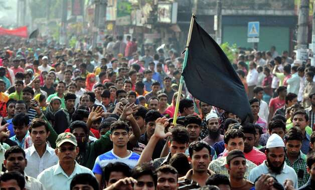 Bangladeshi garments workers take out a protest through a street to mourn the death of the victims of Saturday's fire in a garment factory on the outskirts of Dhaka, Bangladesh, Tuesday, Nov. 27, 2012. Bangladesh held a day of mourning Tuesday for the 112 people killed in the weekend fire, and labor groups planned more protests to demand better worker safety in an industry notorious for operating in firetraps. (AP Photo/Khurshed Rinku) Photo: Khurshed Rinku