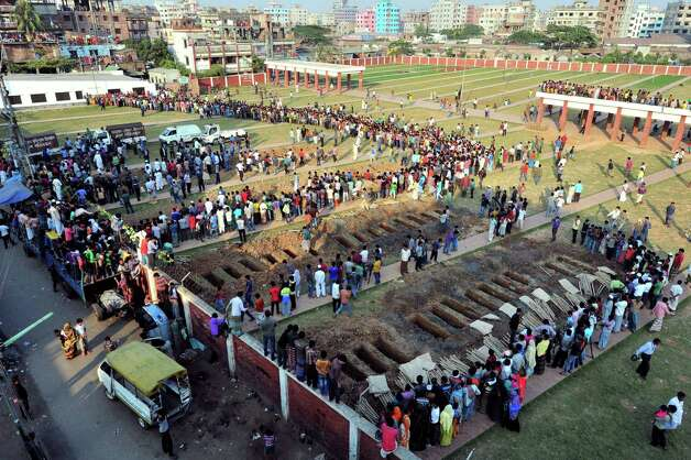 Bangladeshis prepare to bury the bodies of some of the victims of Saturday's fire in a garment factory in Dhaka, Bangladesh, Tuesday, Nov. 27, 2012. Bangladesh held a day of mourning Tuesday for the 112 people killed in the weekend fire at the factory, and labor groups planned more protests to demand better worker safety in an industry notorious for operating in firetraps. (AP Photo/Khurshed Rinku) Photo: Khurshed Rinku