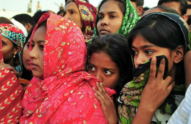 Bangladeshi women watch the bodies of some of the victims of Saturday's fire in a garment factory being prepared to be buried, in Dhaka, Bangladesh, Tuesday, Nov. 27, 2012. Bangladesh held a day of mourning Tuesday for the 112 people killed at the factory, and labor groups planned more protests to demand better worker safety in an industry notorious for operating in firetraps. (AP Photo/Khurshed Rinku) Photo: Khurshed Rinku