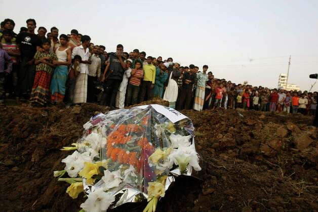 Hundreds of Bangladeshi mourners watch as the bodies of a part of the victims of Saturday's fire in a garment factory are buried in Dhaka, Bangladesh, Tuesday, Nov. 27, 2012. Bangladesh held a day of mourning Tuesday for the 112 people killed in a weekend fire at a garment factory, and labor groups planned more protests to demand better worker safety in an industry notorious for operating in firetraps. (AP Photo/Pavel Rahman) Photo: Pavel Rahman