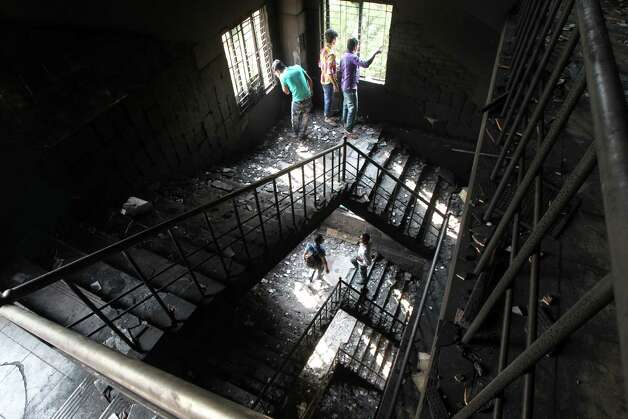 "TOPSHOTS Bangladeshi garment works walk on the burnt stairs of the nine-story Tazreen Fashion plant in Savar, about 30 kilometres north of Dhaka on November 26, 2012. Garment workers staged mass protests to demand the end to ""deathtrap"" labour conditions after Bangladesh's worst-ever textile factory fire, as a new blaze sparked fresh panic and terror. Ahead of the first of a series of mass funerals for the 110 victims, survivors of Saturday night's blaze joined several thousand colleagues to block a highway and march in the manufacturing hub of Ashulia.  AFP PHOTO/ STRSTR/AFP/Getty Images Photo: STR"