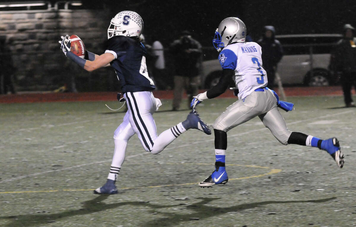 Staples' James Frusciante receives as West Haven's Jawaun Manning closes in as Staples High School hosts West Haven in a Class LL football quarterfinals game in Westport, Conn., Nov. 27, 1012.