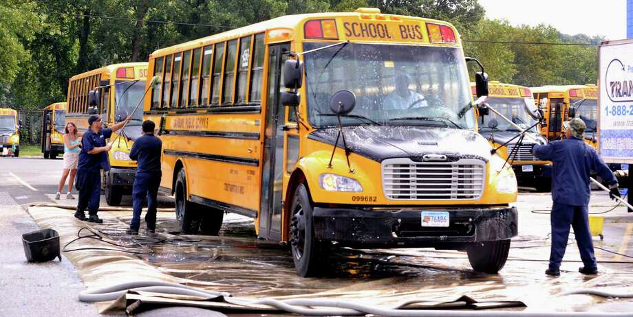 Workers wash Danbury school buses for Student Transportation of America in Danbury, in this file photo. Photo: Michael Duffy, ST / The News-Times