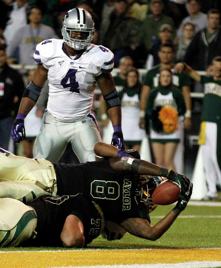 Baylor running back Glasco Martin (8) scores a touchdown over teammate offensive linesman Troy Baker (75) as Kansas State linebacker Arthur Brown (4) watches during the first half of an NCAA college football game Nov. 17, 2012, in Waco. Photo: LM Otero, Associated Press / AP