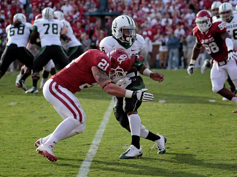 Linebacker Tom Wort #21 of the Oklahoma Sooners hits running back Lache Seastrunk #25 of the Baylor Bears Nov. 10, 2012 at Gaylord Family-Oklahoma Memorial Stadium in Norman, Okla. Oklahoma defeated Baylor 42-34. Photo: Brett Deering, Getty Images / 2012 Getty Images