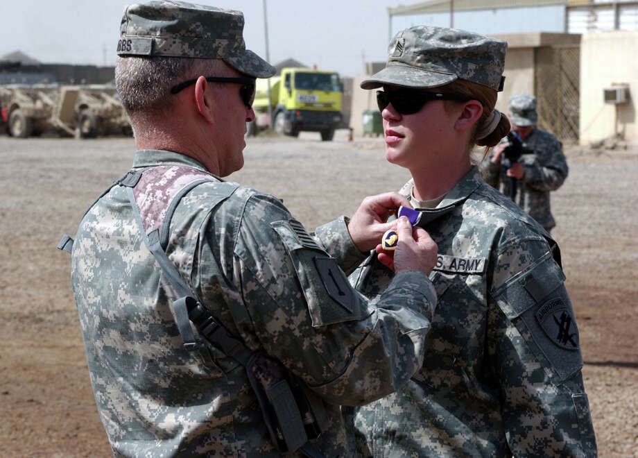 Staff Sgt. Jennifer Hunt, shown here receiving a Purple Heart after being wounded in 2007 while serving in Iraq, is one of several servicewomen who filed suit against the Pentagon's policy barring women from combat positions. Photo: Handout, HO / MCT