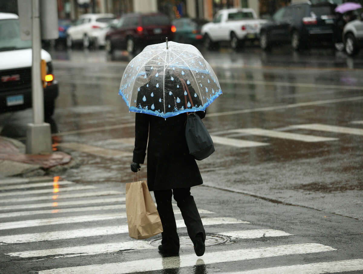 A woman walks in the rain along the Post Road in downtown Fairfield on Tuesday, November 27, 2012.