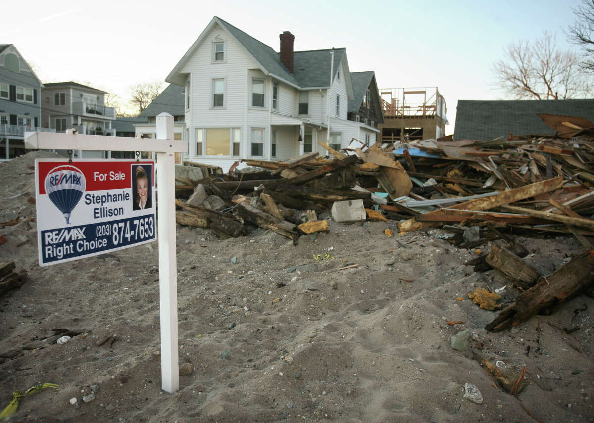 A for sale sign stands on the beach in front of one of the waterfront houses destroyed by Hurricane Sandy in Milford on Monday, November 26, 2012.