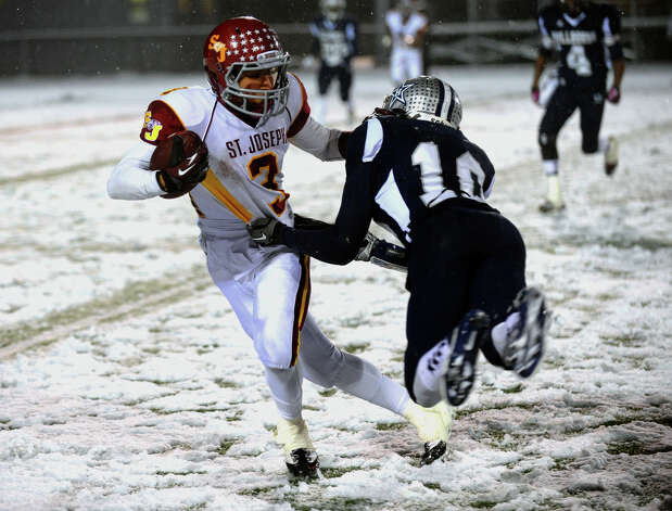 St. Joseph's #3 Jake Pelletier shakes off Hillhouse's #10 Je'Vaughn Moore, during Class M state football quarterfinal action in East Haven, Conn. on Tuesday November 27, 2012. Photo: Christian Abraham / Connecticut Post