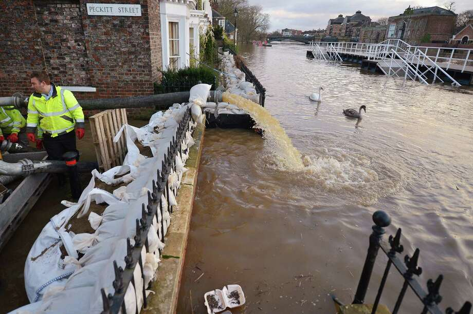 Council woprkers attempt to protect  properties with sandbags and pumps next to the River Ouse on November 27,2012 in York,England. Floodwaters threaten hundreds of homes in Wales and England, as river levels continue to rise exacerbated by further water running into already saturated areas. Photo: Jeff J Mitchell, Getty Images / 2012 Getty Images