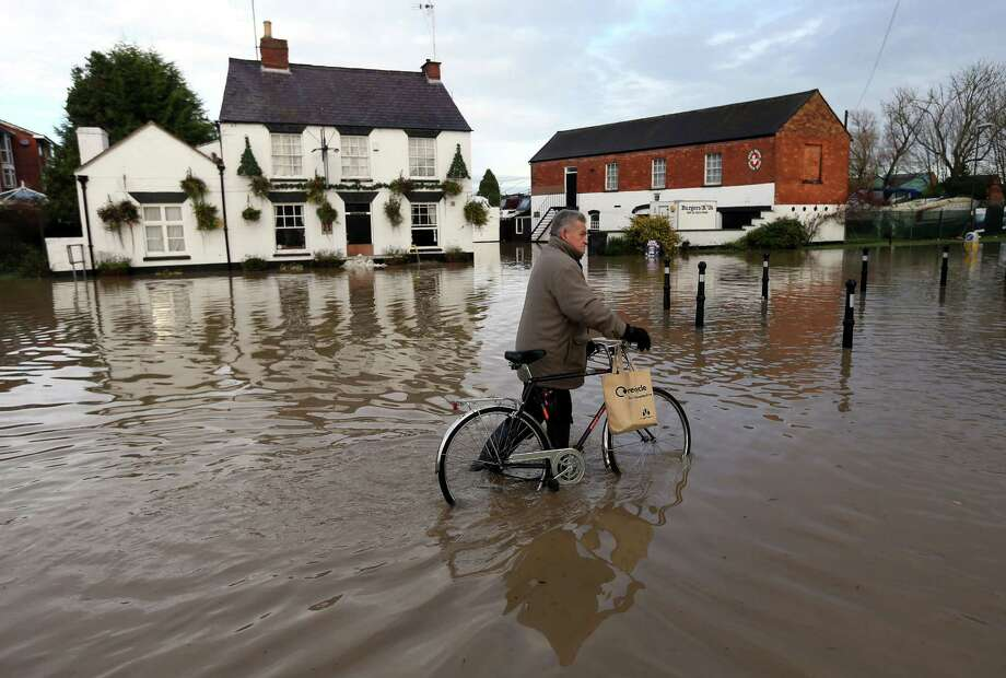 A pedestrian pushes his bike through flood water in  the town Tewkesbury western England Monday Nov. 26, 2012.  Heavy rain and strong winds battered areas of Britain over the weekend, killing two people and flooding 800 homes, officials said Sunday. The southwest of England took the brunt of the bad weather over the weekend, but now the north of England and Scotland are expected suffer from the adverse weather. Photo: David Davies, Associated Press / PA