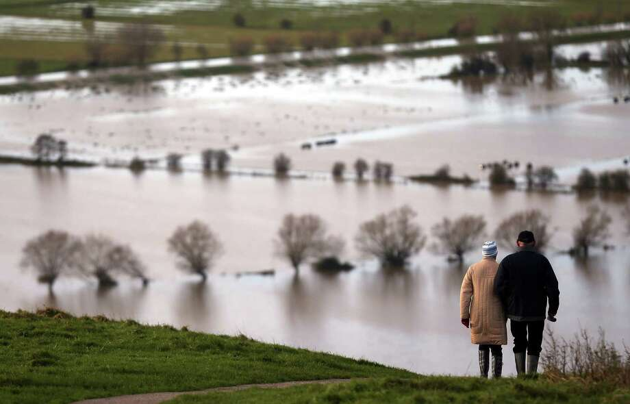 People walk from Glastonbury Tor as flood water in the fields below is seen, on November 25, 2012 in Somerset, England. Another band of heavy rain and wind continued to bring disruption to many parts of the country today particularly in the south west which was already suffering from flooding earlier in the week. Photo: Matt Cardy, Getty Images / 2012 Getty Images