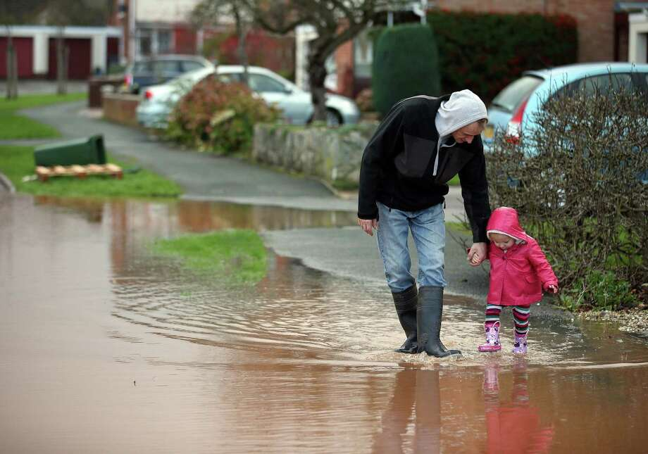 A young girl splashes through flood water in the centre of the village of Ruishton, near Taunton, on November 25, 2012 in Somerset, England. Another band of heavy rain and wind continued to bring disruption to many parts of the country today particularly in the south west which was already suffering from flooding earlier in the week. Photo: Matt Cardy, Getty Images / 2012 Getty Images