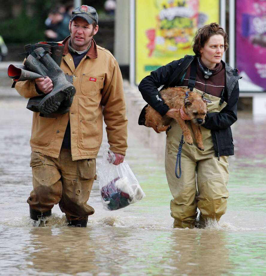 A woman carries her dog as she makes her way through flood waters in St. Asaph, North Wales, Tuesday Nov. 27, 2012, after the town flooded overnight. Thousands of drivers and residents face further chaos today after heavy rain continued to fall across Britain. Photo: Dave Thompson, Associated Press / PA