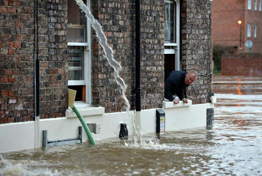 A man watches river levels from The Louther pub as members of the public attempt to protect their properties with sandbags and pumps next to the River Ouse on November 27, 2012 in York, England. Floodwaters threaten hundreds of homes in Wales and England, as river levels continue to rise exacerbated by further water running into already saturated areas. Photo: Jeff J Mitchell, Getty Images / 2012 Getty Images