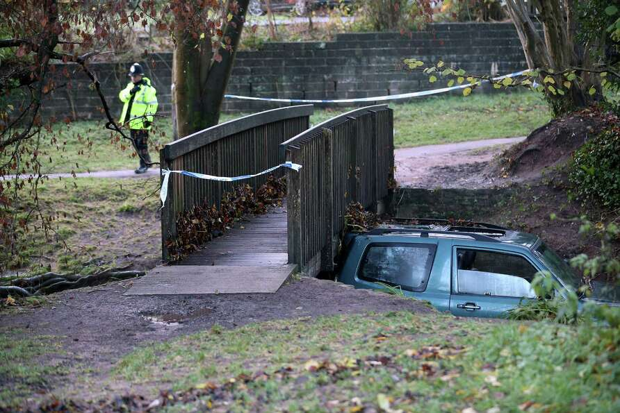 A car, in which a man died after being trapped in flood waters is wedged under a bridge near to a fo