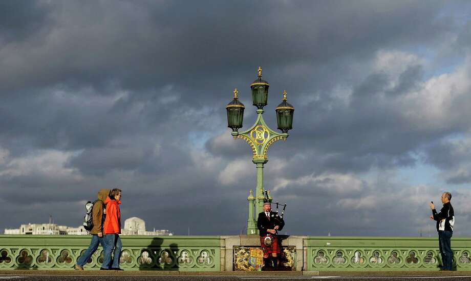 A piper plays on Westminster Bridge as a tourist takes his photograph in central London, Thursday, Nov. 22, 2012. Much of the United Kingdom is facing winds of up to 50-60mph (80-95 kph), and even gusts of up to 70mph (113kph) in exposed western areas, which could worsen surface water flooding as drains are blocked by wind-blown leaves and debris. More wet weather is forecast across the country on Saturday and Sunday. Photo: Alastair Grant, Associated Press / AP