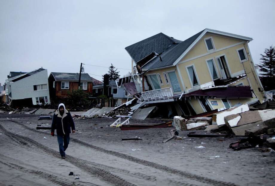 A man walks past destroyed homes on the Rockaway Peninsula in Queens, New York, Tuesday, Nov. 27, 2012.  Officials say New York City's free repair program for storm-damaged homes has fixed up about 50 homes so far, while still just gearing up.  (AP Photo/Seth Wenig) Photo: Seth Wenig