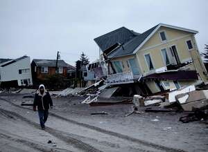 A man walks past destroyed homes on the Rockaway Peninsula in Queens, New York, Tuesday, Nov. 27, 2012.  Officials say New York City's free repair program for storm-damaged homes has fixed up about 50 homes so far, while still just gearing up.  (AP Photo/Seth Wenig)