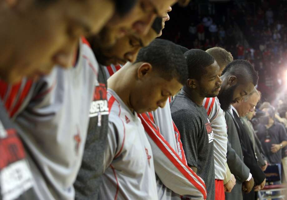 Rockets players pause for a moment of silence before tipoff in honor of Kevin McHale's deceased daughter. (James Nielsen / Houston Chronicle)