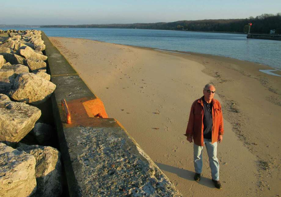 In this Nov. 16, 2012 photo, Jim Simons, who runs a rod and reel repair business in Onekama, Mich., strolls on a sand bar alongside the Portage Lake channel that leads to Lake Michigan at Onekama, Mich.  The sand bar normally would be submerged in water, but low Great Lakes levels have exposed the shoreline in many areas, causing problems for boaters and tourist businesses in small harbor towns. The Great Lakes, the world's biggest freshwater system, are dropping because of drought and climbing temperatures, a trend that accelerated with this year's almost snowless winter and scorching summer. (AP Photo/John Flesher) Photo: John Flesher