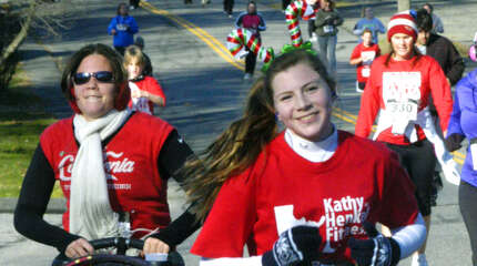 "Erika Henkel, 13, of New Milford sports a winning smile as she picks up the pace during the last half-mile of ""Run, Santa, Run 2 - The Sequel,"" a five-kilometer road race ho"