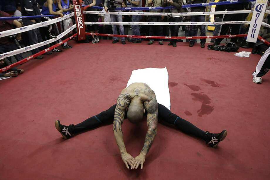 Boxer Miguel Cotto of Puerto Rico stretches following a workout in preparation for his upcoming super welterweight championship fight against Austin Trout at Gleason's Gym in the Brooklyn borough of New York, Tuesday, Nov. 27, 2012.  The fight is Saturday, Dec. 1, 2012, at Madison Square Garden in New  York. Photo: Kathy Willens, Associated Press