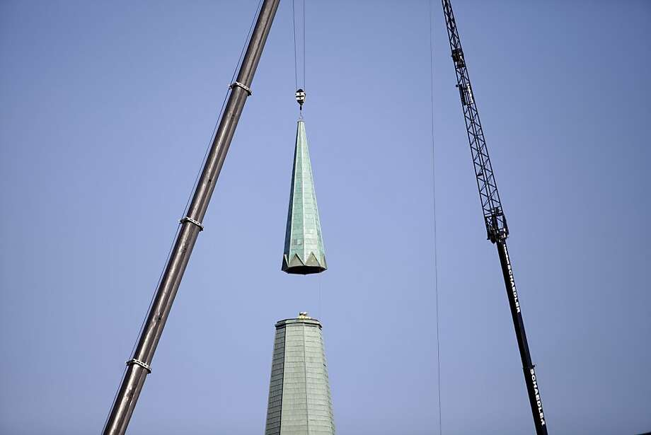 Crews lower a new steeple into place, Tuesday, Nov. 27, 2012, at St. Rose Catholic Church in Perrysburg, Ohio. The nearly 120-year-old church building was struck by lightning during an April thunderstorm, setting the steeple on fire and toppling the cross that sat atop it. Photo: J.D. Pooley, Associated Press