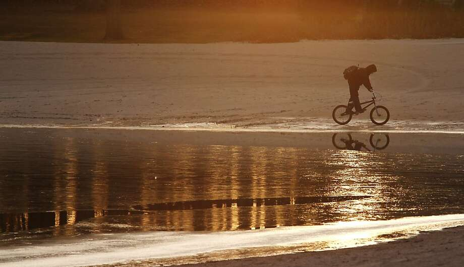 A patron rides their bike across the water coast of the pond at Regner Park as water begins to freeze over in West Bend on Tuesday, Nov. 27, 2012. Photo: John Ehlke, Associated Press