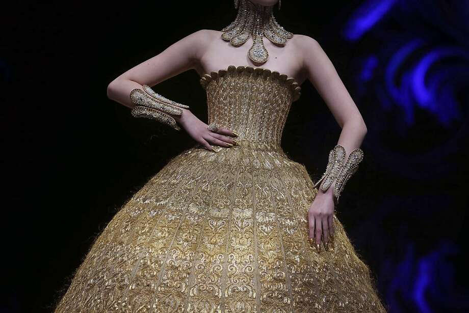 A model showcases a creation by Chinese designer Guo Pei on Tuesday Nov. 27, 2012 in Singapore, during the Asian Couture 2012 Singapore fashion show.(AP Photo/Wong Maye-E) Photo: Wong Maye-E, Associated Press