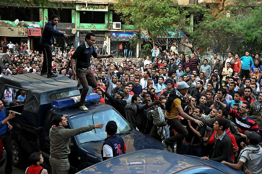Egyptians stand on police vehicles during the funeral of Gaber Salah, who was who was killed in clashes with security forces  in Cairo, Egypt, Monday, Nov. 26, 2012. Thousands of Egyptians on Monday gathered into Cairo's Tahrir Square to attend the funeral of Salah, who was severely injured during clashes with security forces last week and died Sunday night. (AP Photo/Hussein Tallal) Photo: Hussein Tallal, Associated Press