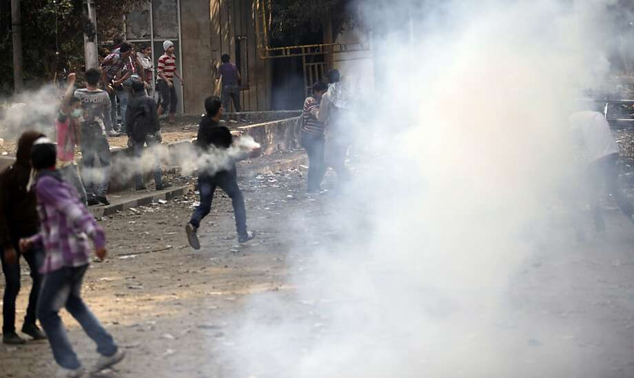 Egyptians clash with security forces and attempt to throw back tear gas canisters fired at them near Tahrir square, where an opposition rally has been called for to voice rejection of President Morsi's seizure of near absolute powers, in Cairo, Egypt, Tuesday, Nov. 27, 2012. The Health Ministry said about 444 people have been wounded nationwide, including 49 who remain hospitalized, since the clashes erupted on Friday, according to a statement carried by the official news agency MENA. (AP Photo/Thomas Hartwell) Photo: Thomas Hartwell, Associated Press