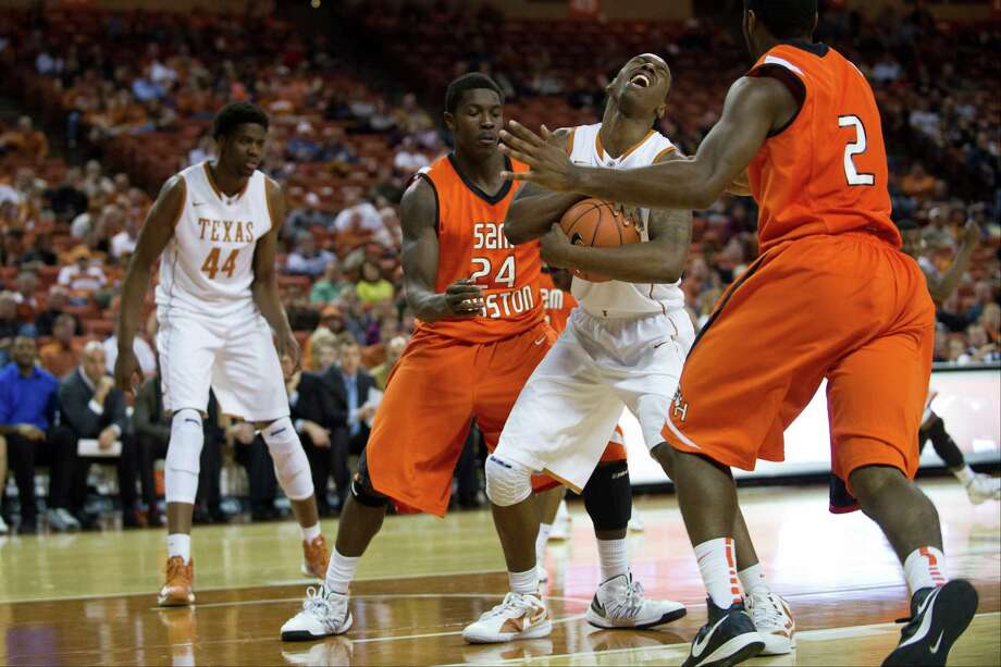 AUSTIN, TX - NOVEMBER 27:  Jonathan Holmes #10 of the University of Texas Longhorns fights for the ball against Terrance Motley #24 of the Sam Houston State Bearkats on November 27, 2012 at the Frank Erwin Center in Austin, Texas. Photo: Cooper Neill, Getty Images / 2012 Getty Images