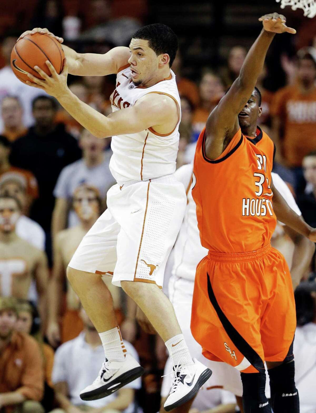 Texas' Javan Felix, left, grabs a loose ball in front of Sam Houston State's Nathaniel Mason, right, during the second half of an NCAA college basketball game, Tuesday, Nov. 27, 2012, in Austin, Texas. Texas won 65-37. (AP Photo/Eric Gay)