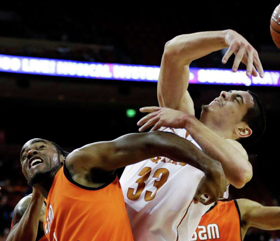 Sam Houston State's Darius Gatson, left, and Texas' Ioannis Papapetrou (33) reach for a rebound during the first half of an NCAA college basketball game, Tuesday, Nov. 27, 2012, in Austin, Texas. (AP Photo/Eric Gay) Photo: Eric Gay, Associated Press / AP