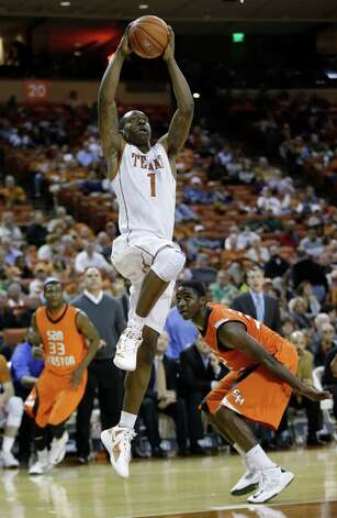 Texas' Sheldon McClellan (1) drives to the basket as Sam Houston State's Nathaniel Mason (33) and Will Bond, right, watch during the second half of an NCAA college basketball game, Tuesday, Nov. 27, 2012, in Austin, Texas. Texas won 65-37. (AP Photo/Eric Gay) Photo: Eric Gay, Associated Press / AP