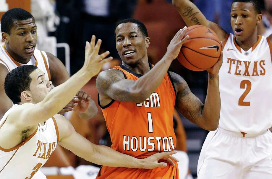 Sam Houston State's Darius Gatson (1) is defended by Texas' Jonathan Holmes, left, Javan Felix (3) and Demarcus Holland (2) during the first half of an NCAA college basketball game, Tuesday, Nov. 27, 2012, in Austin, Texas. (AP Photo/Eric Gay) Photo: Eric Gay, Associated Press / AP