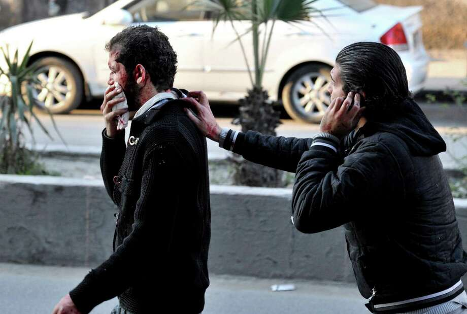 In this photo released by the Syrian official news agency SANA, a Syrian helps a man who was injured after two cars bombs exploded, at Jaramana neighborhood, in the suburb of Damascus, Syria, Wednesday, Nov. 28, 2012. (AP Photo/SANA) Photo: HOPD