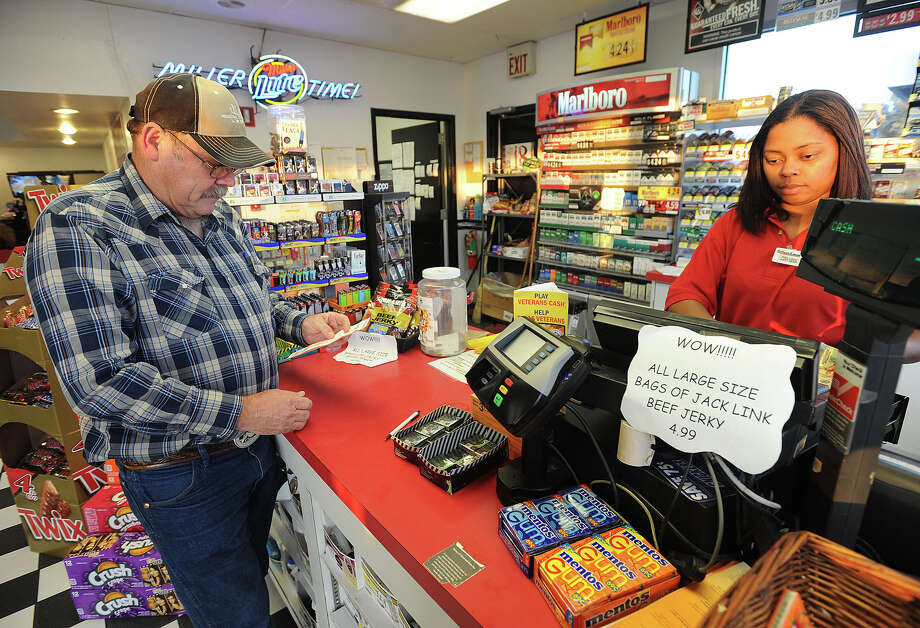 Charles Rice looks over his Powerball ticket while Kaylynn Murry operates the cash register at a U.S. 69 gas station on Tuesday in Beaumont. Players of today's $500 million Powerball have a 1 in 175 million chance in winning the jack pot.   Photo taken Tuesday, November 27, 2012 Guiseppe Barranco/The Enterprise Photo: Guiseppe Barranco, STAFF PHOTOGRAPHER / The Beaumont Enterprise
