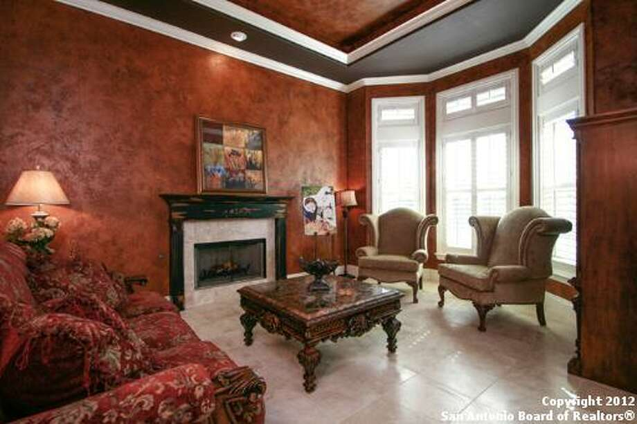 The den's white tile floor, fireplace and large windows usher natural light into the room.