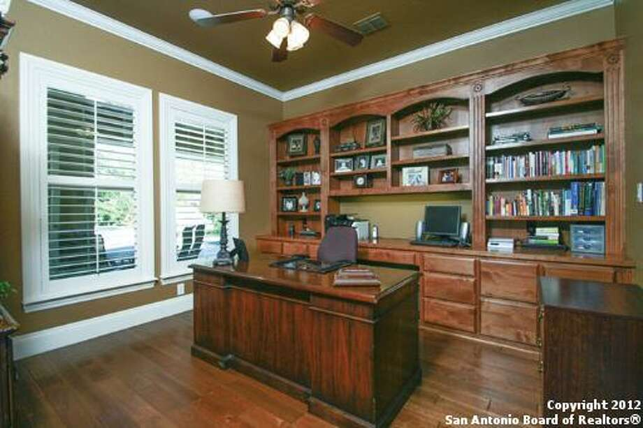 An office bathed in earthy tones and hardwood sports a stately feel.