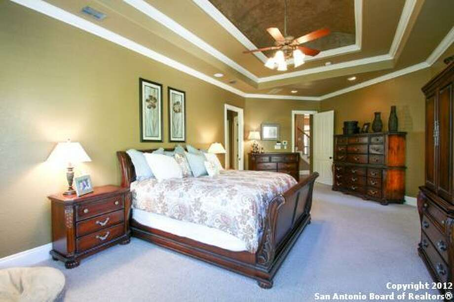 The master bedroom has soaring tray ceilings and an abundance of natural light.