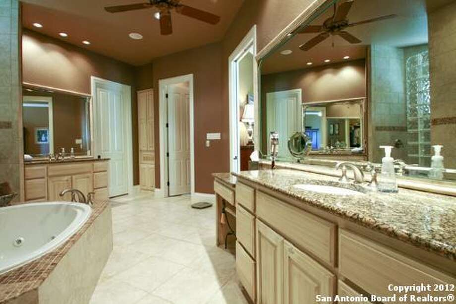 A large soaking tub is nestled in the corner of the master bath, while several vanities allow space for two to get ready in the morning. Notice the separate shower stall in the mirror.
