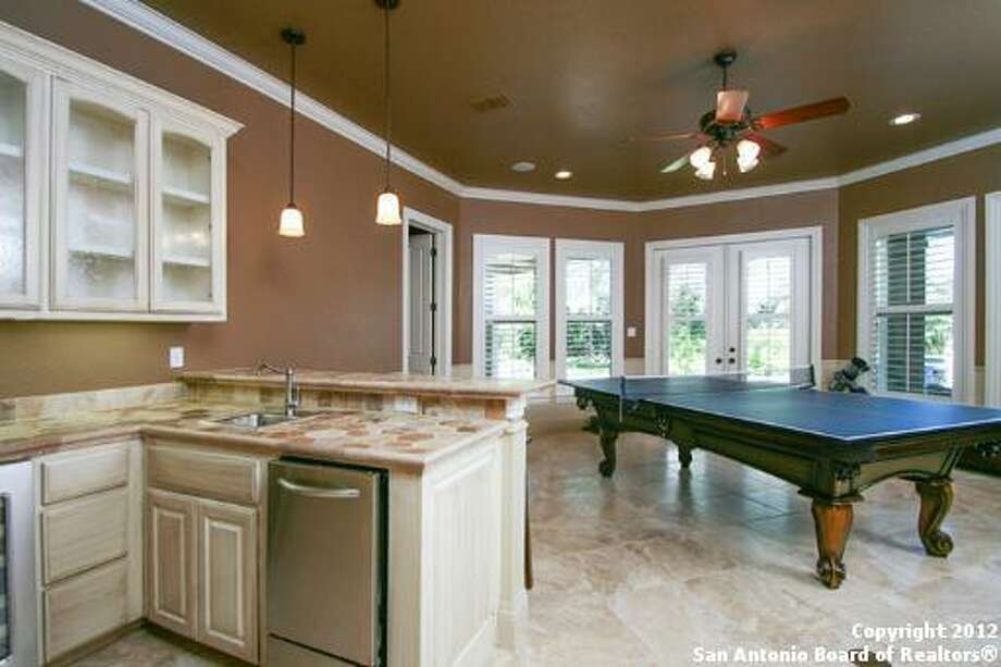 The game room boasts a wet bar in addition to a great deal of cabinet space.
