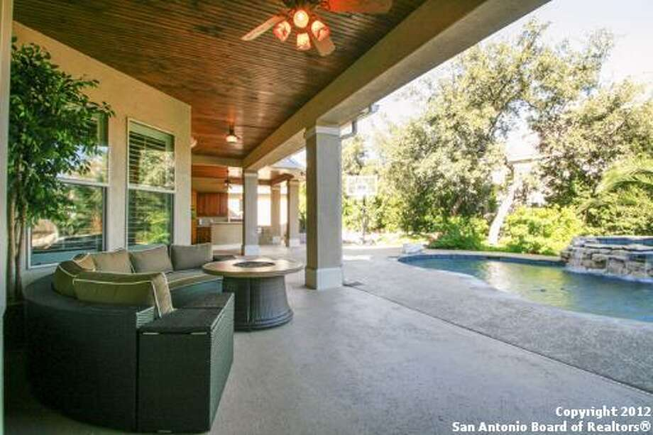 Seen here is the outdoor covered patio, which has a wood slat ceiling and a fire pit.