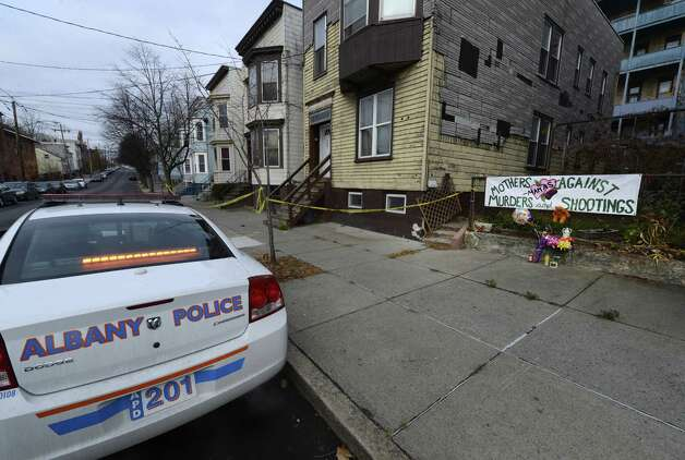 A makeshift memorial was set up for murder victim Tonette Thomas, as well as her sister and aunt, who remain hospitalized from stab wounds, as a lone Albany Police cruiser sits on the street in front of 157 Myrtle Ave. in Albany, N.Y., on Nov 28, 2012, the scene of the attacks.  (Skip Dickstein/Times Union) Photo: SKIP DICKSTEIN